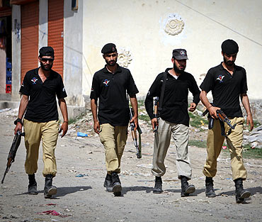 Members of Pakistan's anti-terrorism squad walk past the compound where bin Laden was killed in Abbottabad