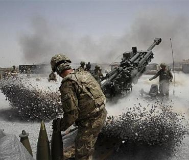 US Army soldiers from the 2nd Platoon, B battery 2-8 field artillery, fire a howitzer artillery piece at Seprwan Ghar forward fire base in Panjwai district, Kandahar province