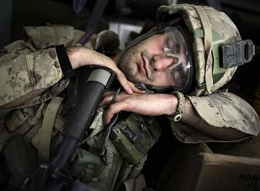 A soldier takes a nap after taking part in an operation in Kandahar