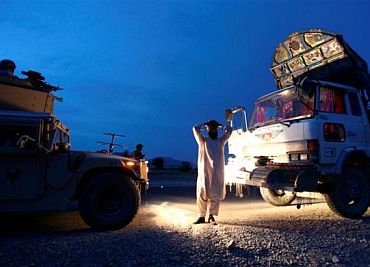 An Afghan man places his hands over his head as US soldiers search his truck for weapons near Sanjaray in Zhari district