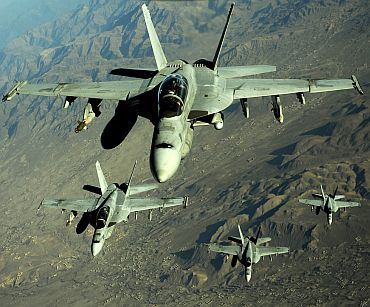 Four US Navy F/A-18 Hornet aircraft fly over mountains in Afghanistan