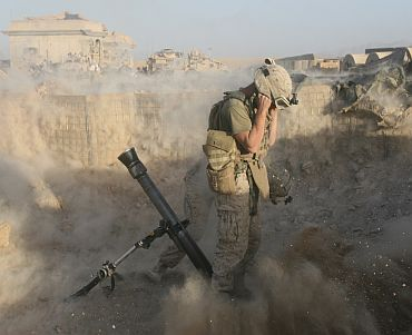 A US Marine fires a mortar round during combat operations at Forward Operating Base Nolay, Afghanistan