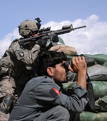 US Army Pfc Ryan L Carson, a member of the company intelligence support team of Alpha Company, 1st Battalion, 327th Infantry Regiment, Task Force Bulldog, and an Afghan police officer search a hillside at the Shege East Afghan National Police Checkpoint in the Kunar province of Afghanistan prior to a firefight. Approximately two dozen insurgents fired rocket-propelled grenades, heavy machine guns and small arms at the post