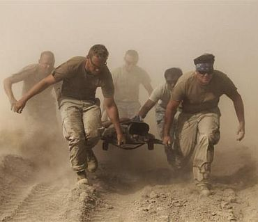 Members of the US Navy carry a comrade wounded by an explosion to a medevac helicopter in Kandahar province in southern Afghanistan