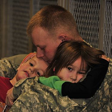 Pfc Chris Paterson, a native of Hudson, Ohio, holds his daughter Aliva and son Foster before deploying to Afghanistan from Fort Drum, New York. Paterson is an infantryman assigned to Charlie Company, 2nd Battalion, 22nd Infantry Regiment of the 10th Mountain Division's 1st Brigade Combat Team.