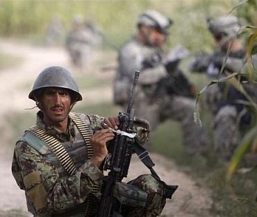 An Afghan army soldier takes up position during a joint patrol with US army soldiers from Delta Company, a part of Task Force 1-66, near the village of Mohammad D'Jakub, Arghandab River valley, Kandahar province