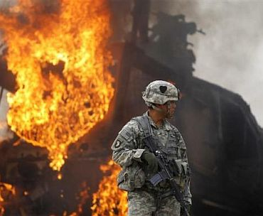 Captain Melvin Cabebe with the US Army's 1-320 Field Artillery Regiment, 101st Airborne Division stands near a burning M-ATV armored vehicle after it struck an improvised explosive device near Combat Outpost Nolen in the Arghandab Valley north of Kandahar