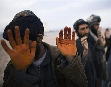 Afghan men wait to be searched at a checkpoint at Delaram district in Nimroz province