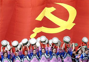 Actresses of Tujia minority dance as they sing Chinese revolutionary songs in front of a giant flag of the Communist Party of China during a performance to celebrate CPC's 90th anniversary