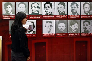 A woman helps to prepare an exhibition about the history of China's Communist Party at the Shanghai Exhibition Centre