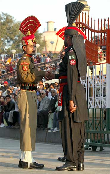 A Pakistani Ranger and an Indian Border Security Force officer shake hands at the Wagah border post