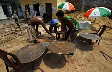 Labourers prepare metal campaign props in the shape of flowers, a symbol of the Trinamool Congress in West Bengal