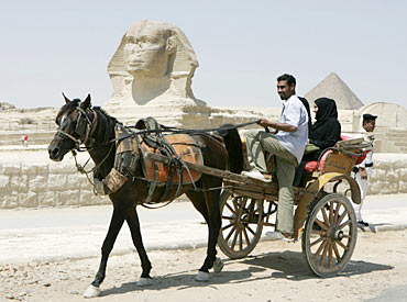 A horse drawn carriage passes in front of the Sphinx at The Pyramids of Giza in Egypt