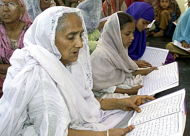 Riot victims read the Holy Koran during a prayer ceremony in Ahmedabad,