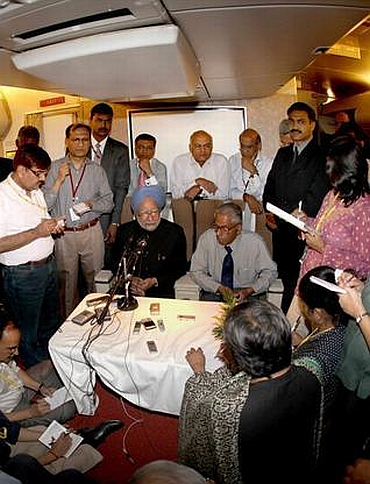 Dr Singh interacts with journalists on board his special aircraft in 2009 along with his then NSA MK Narayanan