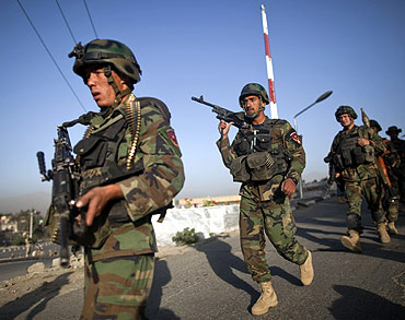 Afghan National Army soldiers leave the Intercontinental hotel area after a battle between security forces and suicide bombers in Kabul