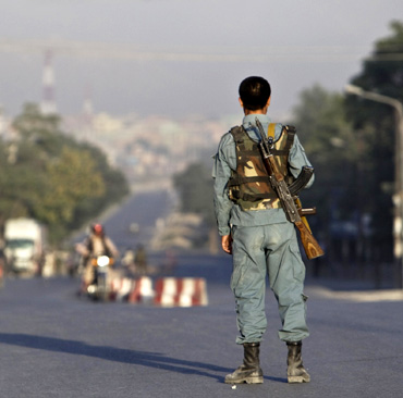 An Afghan policeman keeps watch on a road leading to the Intercontinental hotel during a battle between Afghan security forces and suicide bombers in Kabul