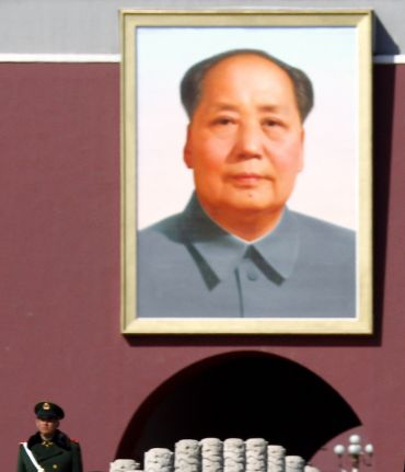A paramilitary policeman stands guard in front of a giant portrait of the late Chairman Mao Ze