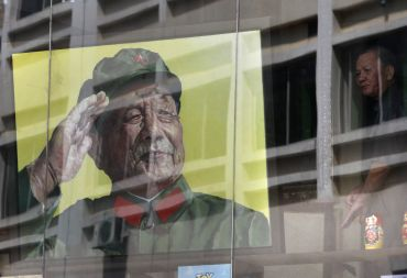 A man looks out from a window next to a portrait of late Chinese leader Deng Xiaoping.
