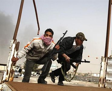 Anti-government tribal rebels prepare for possible attacks by pro-Gaddafi loyalists at a checkpoint in Ajdabiya area, southwest of Benghazi