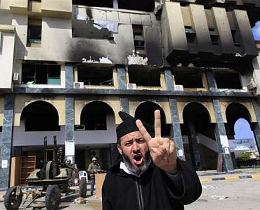 A protester gestures near soldiers opposed to Libya's leader Muammar Gaddafi outside the burnt governor's office in the city of Zawiyah