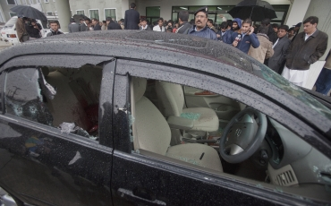 Police and members of the media stand near the bullet-riddled car of slain Pakistan's Minister for Minorities Shahbaz Bhatti outside the emergency ward of a hospital in Islamabad