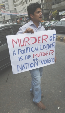 A supporter of the South Asia Forum for Human Rights holds a placard during a protest in Karachi