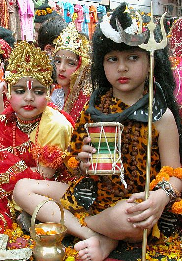 A boy dressed as God Shiva sits during a religious procession in Jammu.