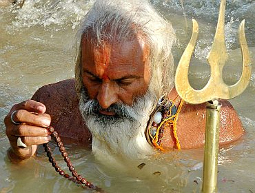 A sadhu offers prayer to Lord Shiva in the river Ganga in Allahabad.