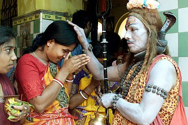 A man dressed as Lord Shiva blesses a devotee on the occasion of Shivratri in Trakeshawar, West Bengal
