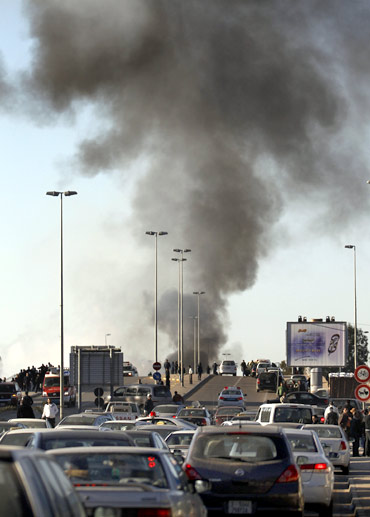 Smoke rises from a burning fuel truck as traffic is rerouted in Tripoli