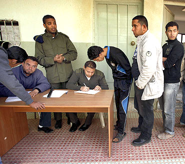 Civilians who have volunteered to join the rebel army register their names in a school in Benghazi