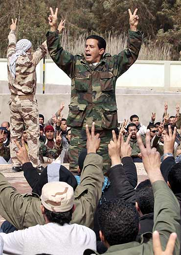 Civilians who have volunteered to join the rebel army shout anti-Gaddafi slogans at a school in Benghazi