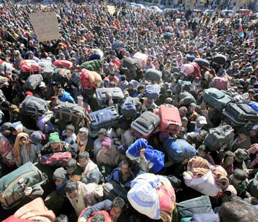 Migrant workers wait near the Tunisian gate after fleeing the unrest in Libya