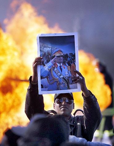 A man holds up a poster of Libya's leader Muammar Gaddafi