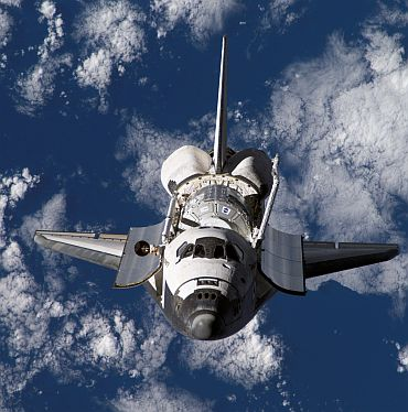 Backdropped by a blue and white Earth, Space Shuttle Discovery approaches the International Space Station during rendezvous and docking operations