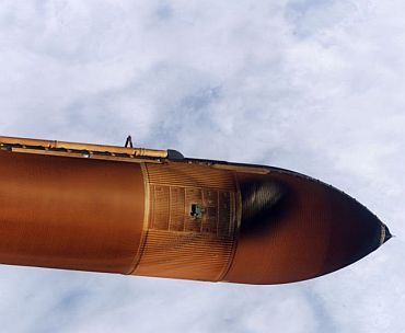 Handheld still image taken by Discovery's crew of the external fuel tank as it was jettisoned after launch were transmitted to the ground early July 27. Initial analysis of the imagery shows a large piece of foam that separated from the tank during the Shuttle's ascent to orbit. The foam detached from an area of the tank called the Protuberance Air Load (PAL) Ramp. In this still image, the area of missing foam on the tank is indicated by a light white spot in near the upper edge of the tank just below the liquid oxygen feedline