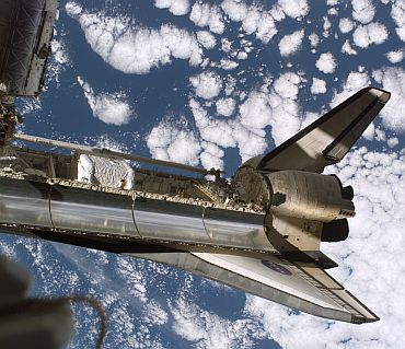 Backdropped by a cloud-covered Earth, Space Shuttle Discovery is featured in this image while docked with the International Space Station during the STS-116 mission