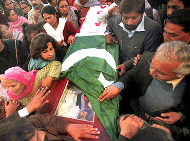 People gather near the casket of Pakistan's Minister for Minorities Shahbaz Bhatti, wrapped in national and party flags, after a funeral ceremony inside a church in Islamabad