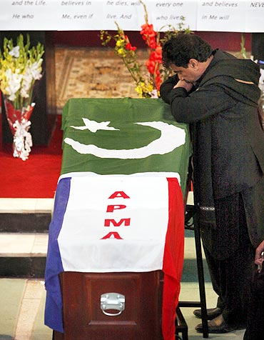 Jerald Bhatti, a brother of Pakistan's slain Minister for Minorities Shahbaz Bhatti, stands next to his casket, wrapped in national and party flags, during a funeral ceremony inside a church in Islamabad