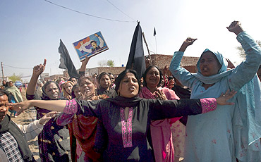 Women hold a picture of Pakistan's slain Minorities Minister Shahbaz Bhatti as they mourn near his family residence in the village of Khushpur
