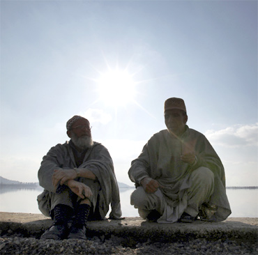 Two men chat on the banks of Dal Lake in Srinagar