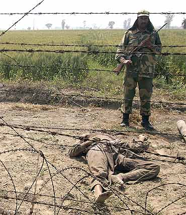 A BSF soldier stands next to the body of a suspected smuggler near the border with Pakistan