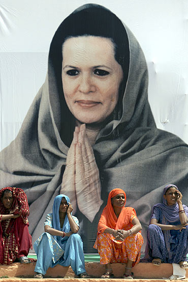 Women sit in front of a poster of Sonia Gandhi