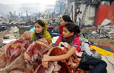 Rubina Ali (right ), who acted as young Latika in the Oscar-winning film Slumdog Millionaire, sits with her family amid the ruins of the Gharib Nagar slum