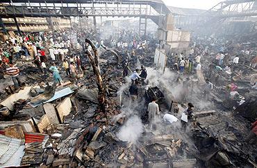 Residents search for their belongings amid the ruins of the Gharib Nagar slum