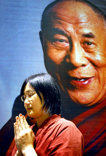 A follower prays in front of a picture of the Dalai Lama