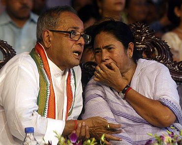 Union Finance Minister Pranab Mukherjee speaks with Trinamool chief Mamata Banerjee in a rally in Kolkata