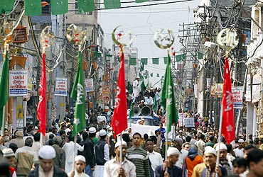 Muslims hold religious flags as they take part in a procession to mark Eid-e-Milad-ul-Nabi in the old quarters of Delhi