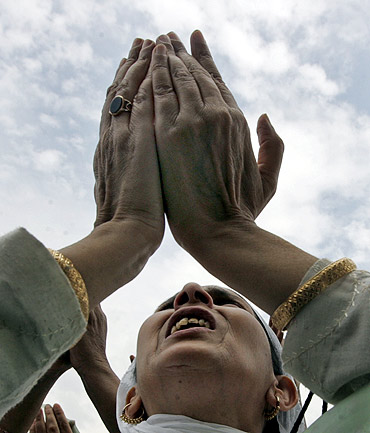 A Kashmiri Muslim woman raises her arm in prayer as a cleric displays (unseen) a relic of Prophet Mohammed following celebrations for 'Meeraj-un-Nabi' at the Hazratbal shrine in Srinagar